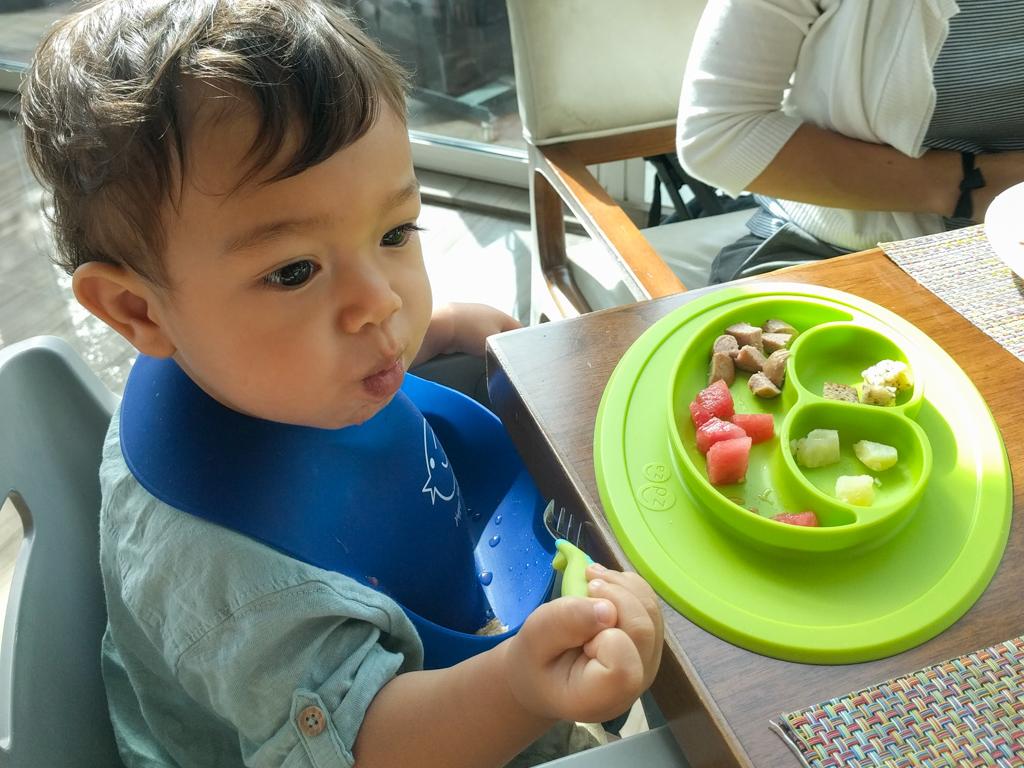 Toddler baby feeding himself on a trip to Dubai
