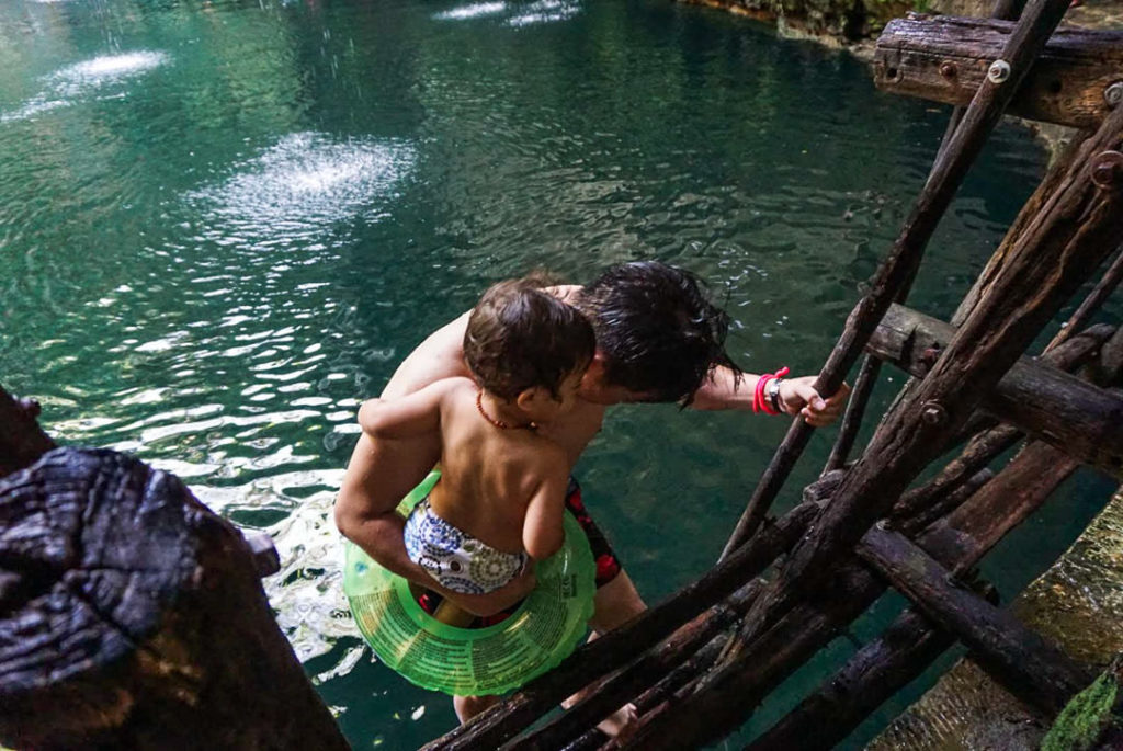 Dad carrying toddler down ladder into cenote pool