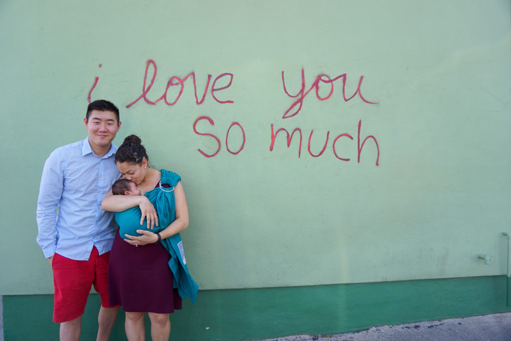 Young mixed family mom kissing newborn baby in front of I love you so much mural on South Congress Street in Austin