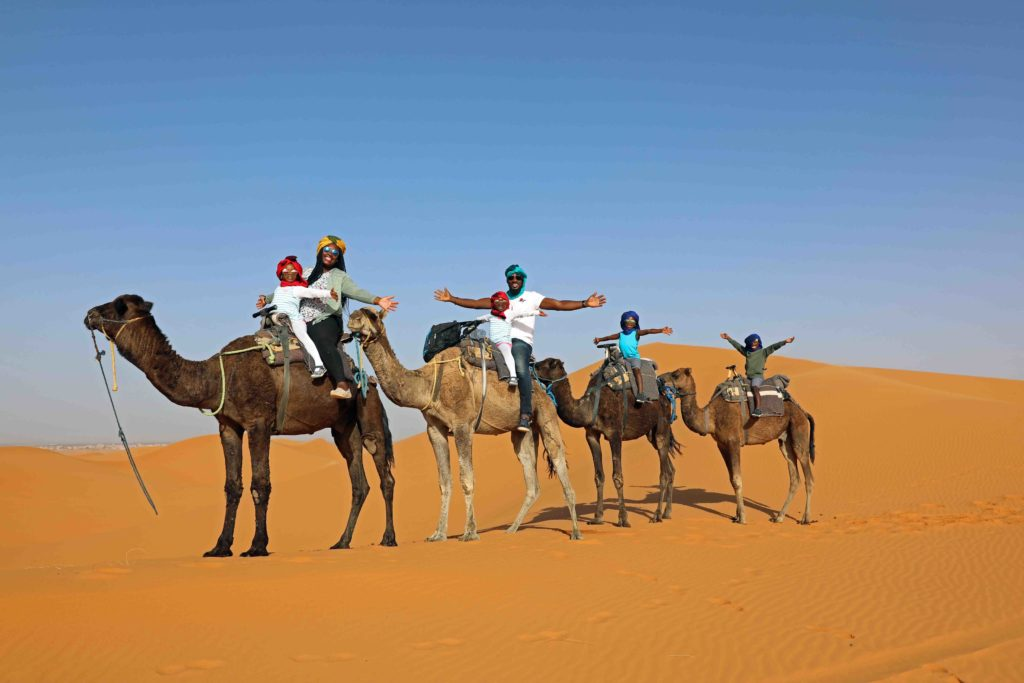 Black family traveling with kids on a camel ride through the Sahara Desert - diversity in family travel