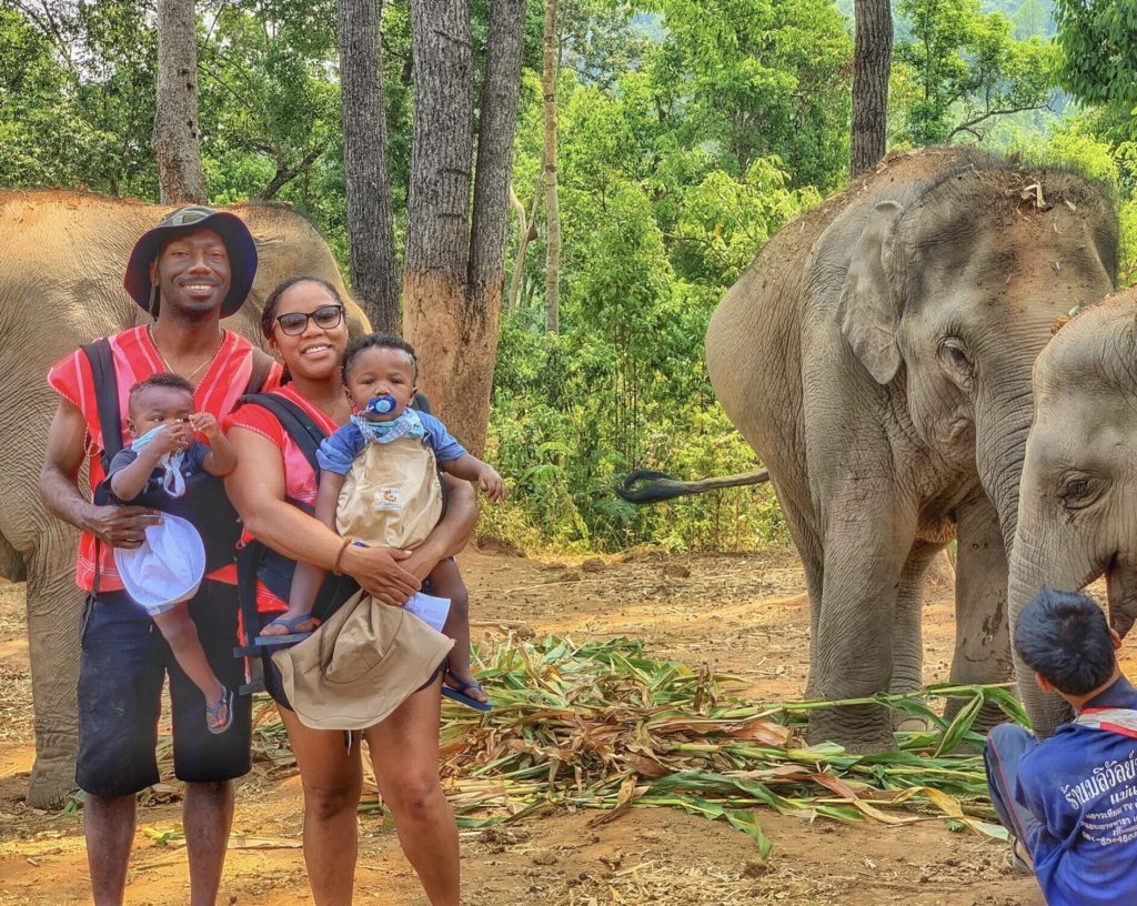 Young Black family with twins traveling in Thailand seeing elephants - diversity in family travel
