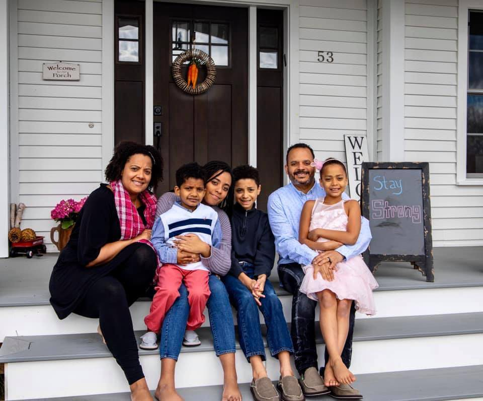 Black multiethnic family in front of house