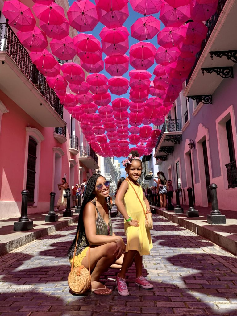 Mom and daughter under pink umbrella street traveling - diversity in family travel