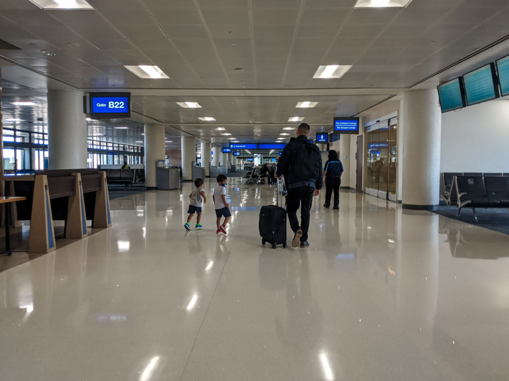 Dad with suitcase with two young kids - flying with a toddler in a pandemic