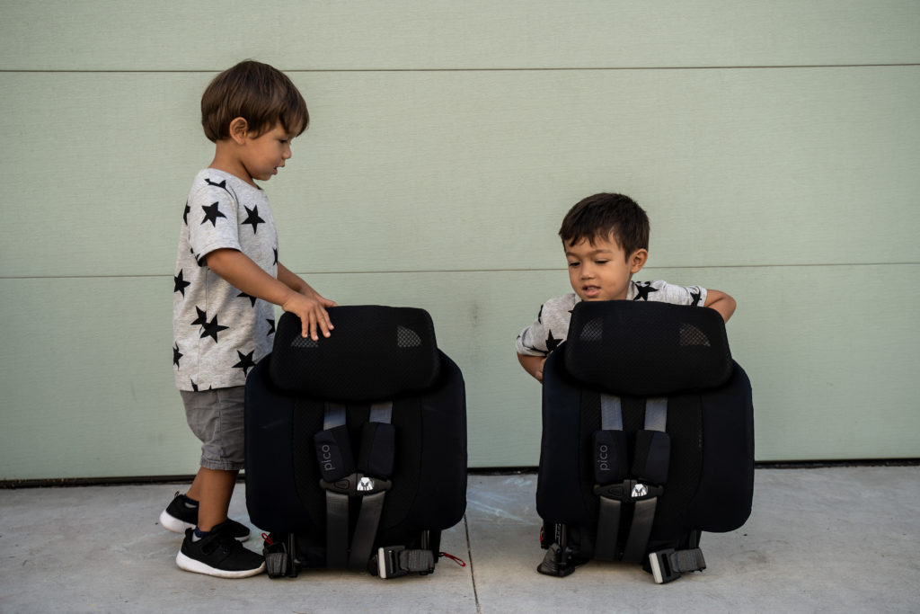 Toddler brothers checking out their new compact folded WAYB Pico travel car seats